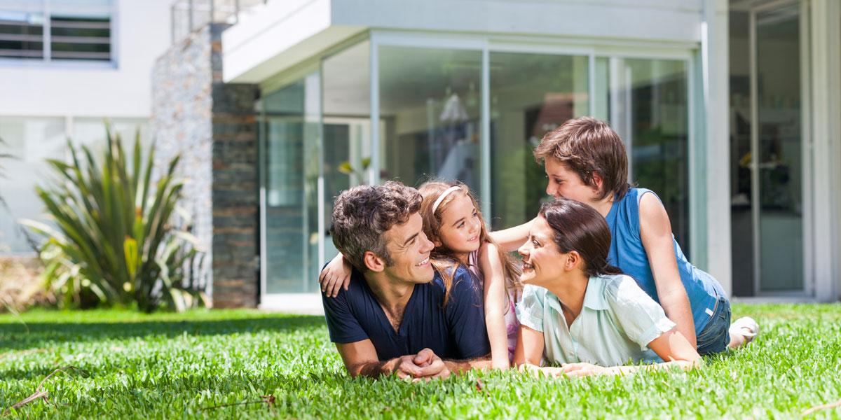 Familie liegt am Rasen vor ihrem Einfamilienhaus