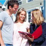 Immobilienmaklerin mit jungem Pärchen vor Einfamilienhaus